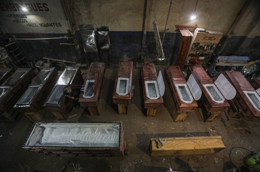 Peruvian migrant coffin maker Cesar Ambrosio finishes the details on a production line of coffins at the Bergut Funeral Services in Santiago, Chile, Thursday, June 18, 2020. The coffin production has had to increase up to 120%, according to Nicolas Bergerie, owner of the factory. His more basic coffin model is called the COVID model and is made to cope with the increase of deaths during the coronavirus pandemic. (AP Photo/Esteban Felix)