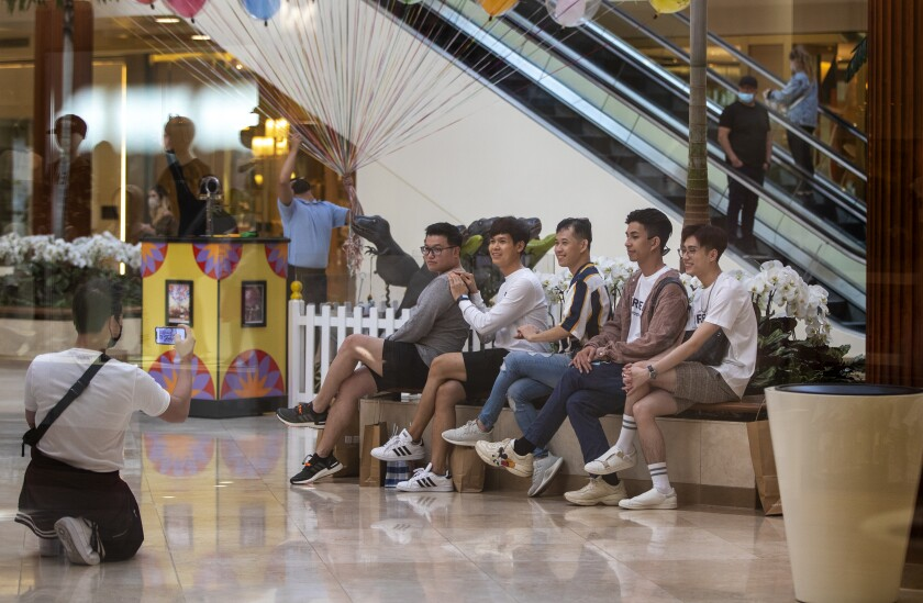 Shoppers line up on a bench for a group photo.