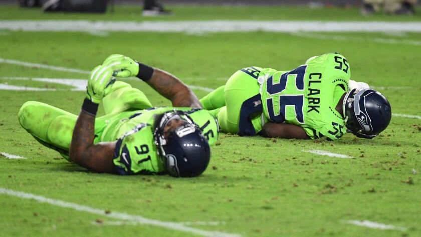 Defensive end Frank Clark and defensive tackle Sheldon Richardson of the Seattle Seahawks both lay on the field after a play.