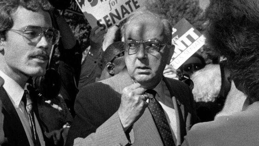 Sen. Jesse Helms, a figure renowned for his role in the culture wars of the '80s and '90s, shakes a fist at reporters in Raleigh, N.C., in 1990.
