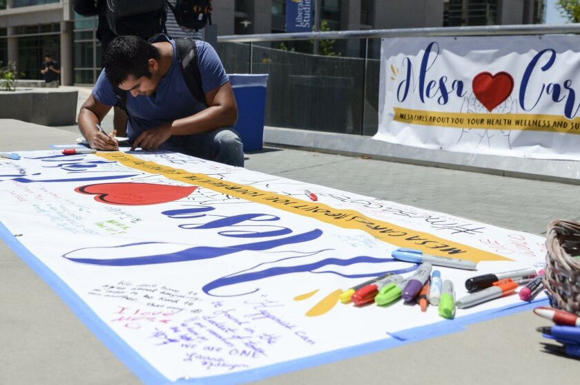 A student writes a message on a Mesa Cares banner at Mesa College. The new Mesa Cares initiative is a way for the school to respond whenever traumatic events happen in the nation or world.