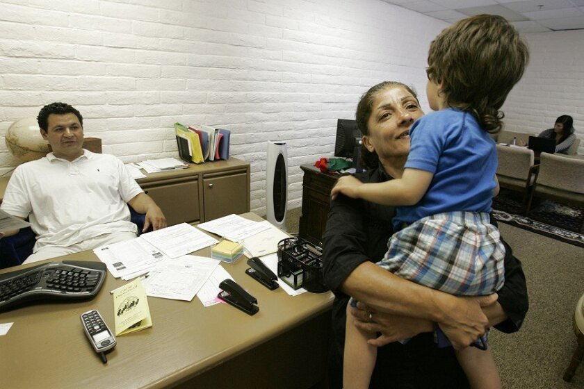 The East County Refugee Center helps immigrants adjust to life in the U.S. Ahlam Peteurs and her son, Samer Mikha, 3, met with ILdefonso Espinoza, (left), secretary for the center.