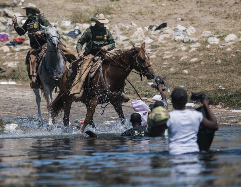 Guardias fronterizos a caballo tratan de impedir el paso de migrantes que cruzan el río Bravo