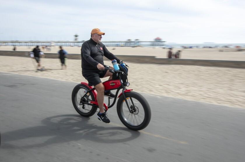 A man rides an e-bike on the bike path in Huntington Beach on Wednesday.