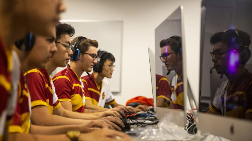 Members of the USC varsity esports team are reflected in the screens of their monitors during practice in a basement lab.