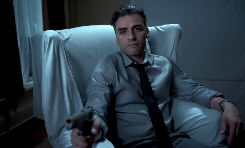 """A man seated in a chair points a pistol in the movie """"The Card Counter."""""""