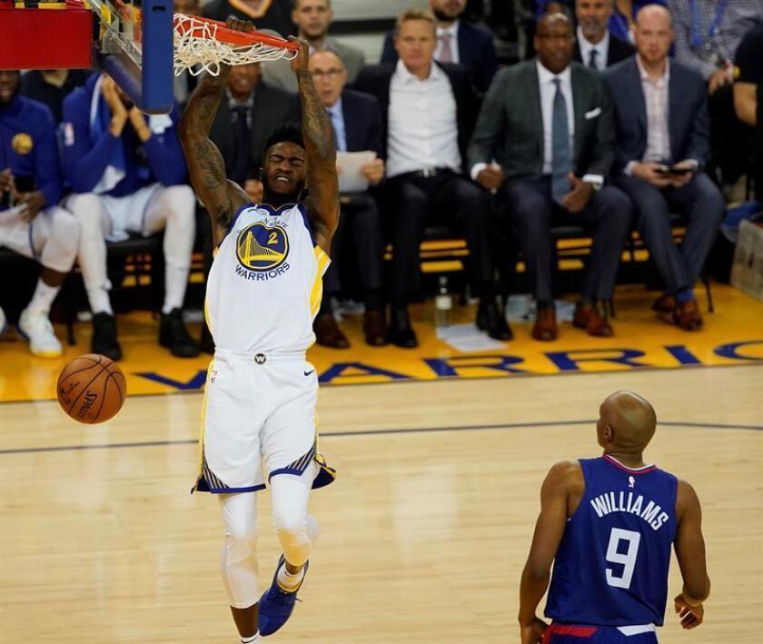 El jugador de los Warriors Jordan Bell (i) lucha por el balón con C.J. Williams (c), de los Clippers, durante el partido de la NBA que enfrentó a Los Angeles Clippers y los Golden State Warriors en el Oracle Arena en Oakland, California (Estados Unidos). EFE