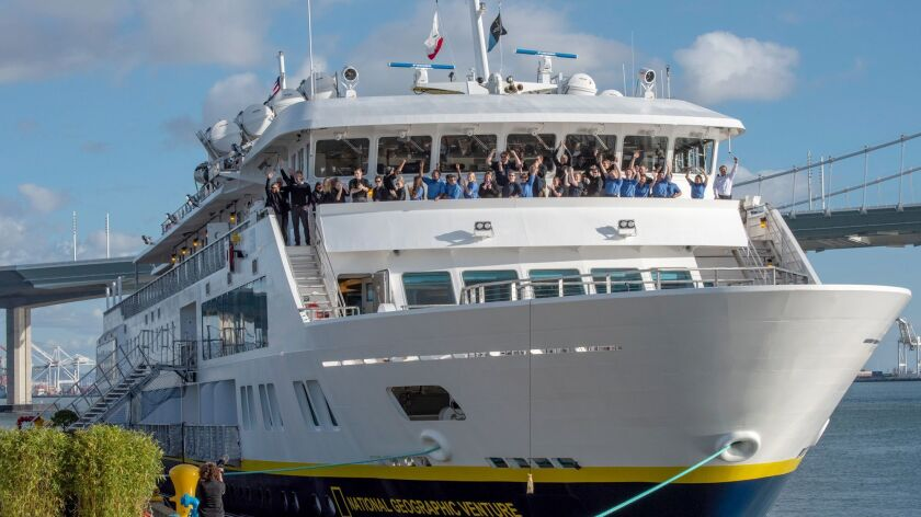 Officers and crew cheer during the christening of the National Geographic Venture at Treasure Island in San Francisco Bay.