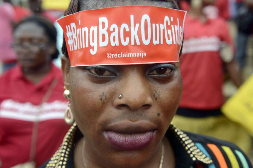 "A woman with a sticker on her head bearing the slogan ""Bring back our girls"" marches for the release of the 272 abducted schoolgirls."