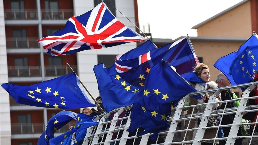 Anti-Brexit activists fly EU and Union flags from the Millennium Bridge in Newcastle, England on March 15.