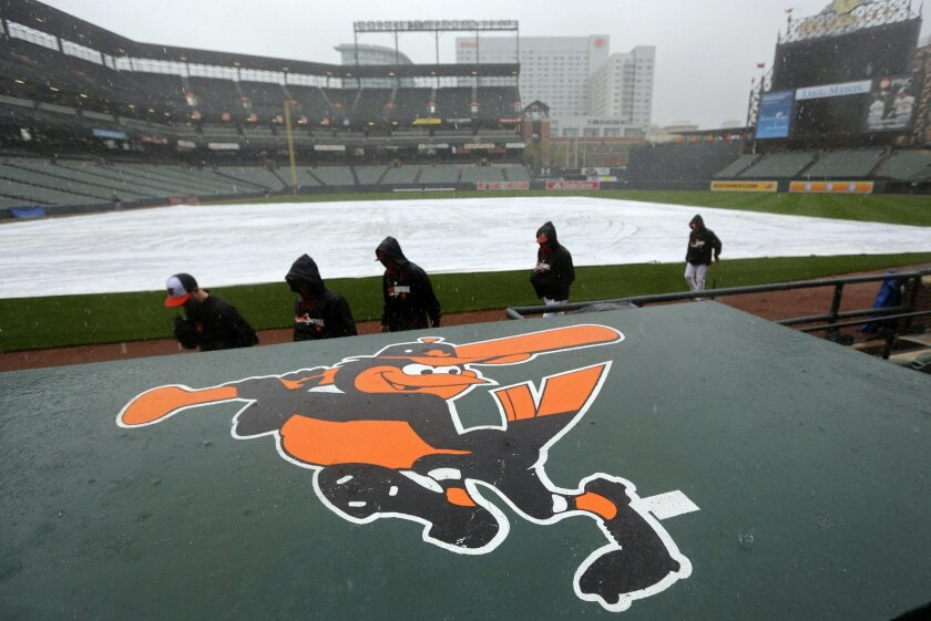 Members of the Baltimore Orioles walk into the dugout for shelter from the rain before a scheduled baseball game between the Orioles and the Pittsburgh Pirates, Tuesday, April 29, 2014, in Baltimore. Officials postponed the game due to the rain, and it has been rescheduled for Thursday. (AP Photo/P
