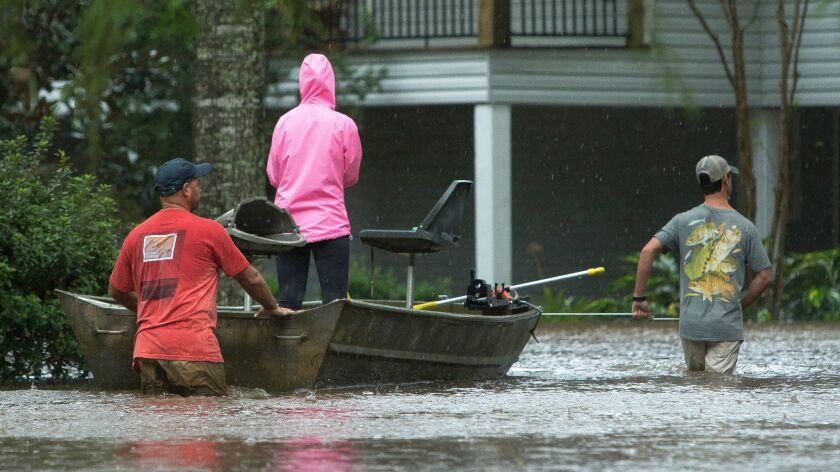 Residents of Cypress Lake Dr. use boats to transport others and retrieve items from flooded homes in