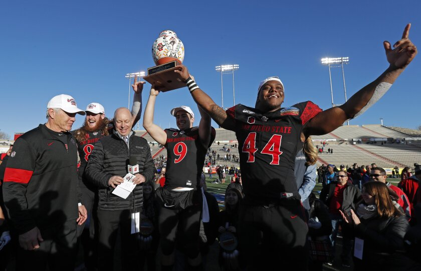 San Diego State linebacker Kyahva Tezino (44), quarterback Ryan Agnew (9), tight end Parker Houston, second from left, and coach Rocky Long, left, celebrate with the New Mexico Bowl trophy after beating Central Michigan.