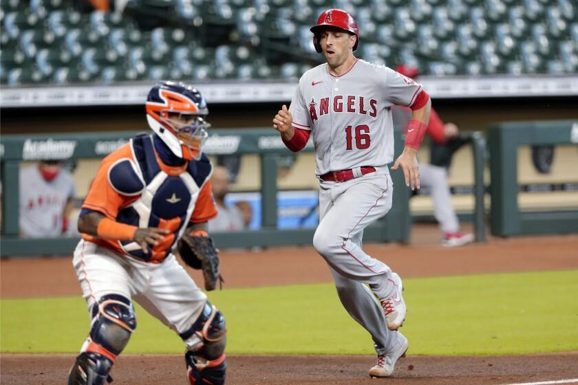 Angels' Jason Castro scores behind Houston Astros catcher Martin Maldonado during a game on Tuesday.