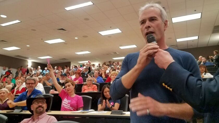Rick Somers, 53, a small-business owner, asks Republican Rep. Buddy Carter a question about the Affordable Care Act at a town hall in Savannah , Ga.