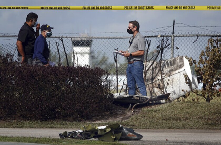 NTSB investigators work the scene of a plane crash near North Perry Airport in Pembroke Pines, Fla. Tuesday, March 16, 2021. A four-year-old child riding in a vehicle on the ground and the pilot and passenger in the plane were killed. (Joe Cavaretta/South Florida Sun-Sentinel via AP)