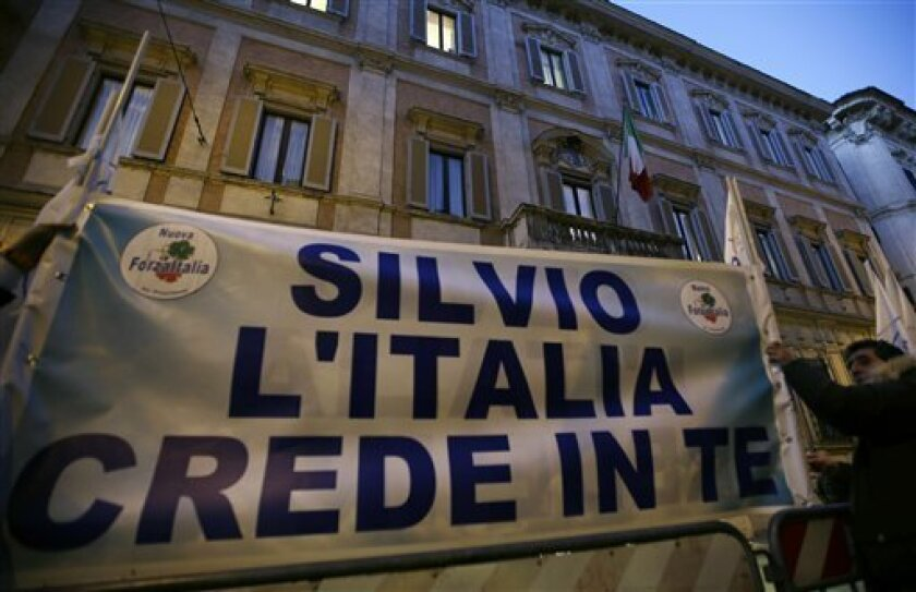 """Supporters of former Italian premier Silvio Berlusconi expose a banner reading """"Silvio Italy trusts you"""" in front of Palazzo Grazioli, the residence of Berlusconi, in Rome, Thurdsday, Dec. 6, 2012. The 76-year-old Berlusconi has been hinting at a comeback, after earlier saying he would leave the party to a younger candidate. Berlusconi claims allies are pressing him to return, hoping that Monti's painful austerity measures will win votes for the center-right. Lawmakers belonging to Silvio Berlusconi's center-right party abstained Thursday from a confidence vote in the government of Premier Mario Monti, raising questions over its future and the progress of its economic reform program. (AP Photo/Alberto Pellaschiar)"""