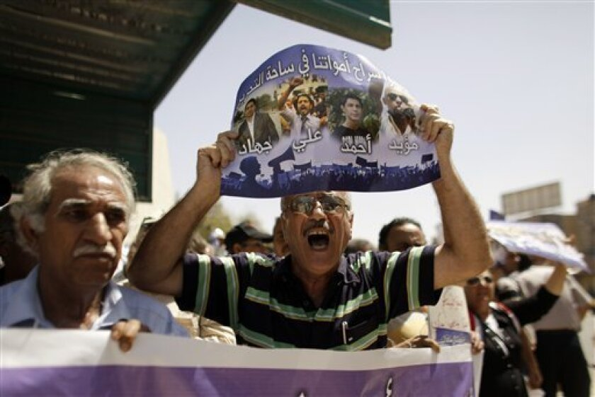 """A man chants slogans as he holds a poster depicting four detained activists with the words """"release our voice in Tahrir Square,"""" in Arabic, at a demonstration calling for their release in Tahrir Square in central Baghdad, Iraq, Friday, June 3, 2011. A leading human rights group says Iraq's central government and regional Kurdish leaders are beating and illegally detaining protesters to try to stop demonstrations calling for reforms. (AP Photo/Maya Alleruzzo)"""