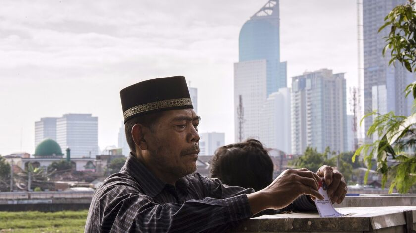 An man casts his ballot in the governor's election at a polling station in Jakarta, Indonesia, on We