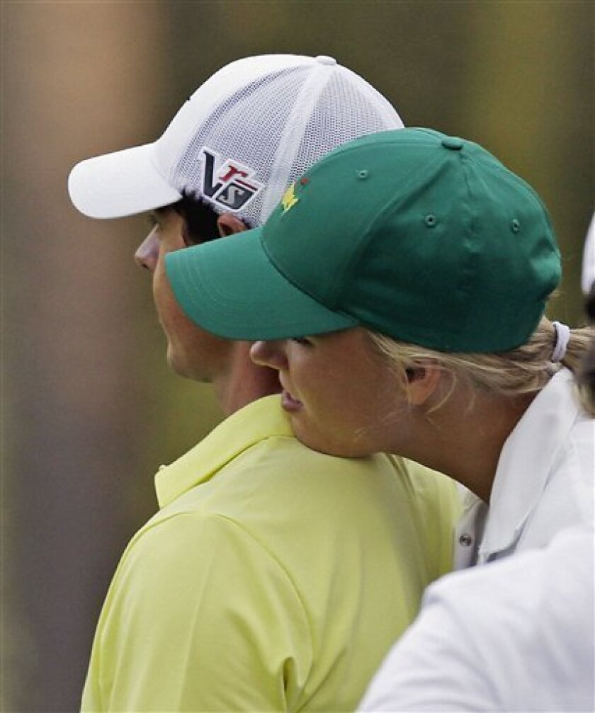Tennis player Caroline Wozniacki rests her head on Northern Ireland's Rory McIlroy's shoulder during the par three competition before the Masters golf tournament Wednesday, April 10, 2013, in Augusta, Ga. (AP Photo/David J. Phillip)