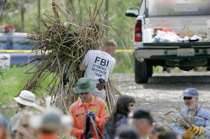 Law enforcement personnel prepare to search a pond at the southwest edge of Kit Carson Park. An FBI agent carries some of the brush that was cleared at the pond's edge to assist the search as investigators follow up on a lead in the Amber Dubois investigation.