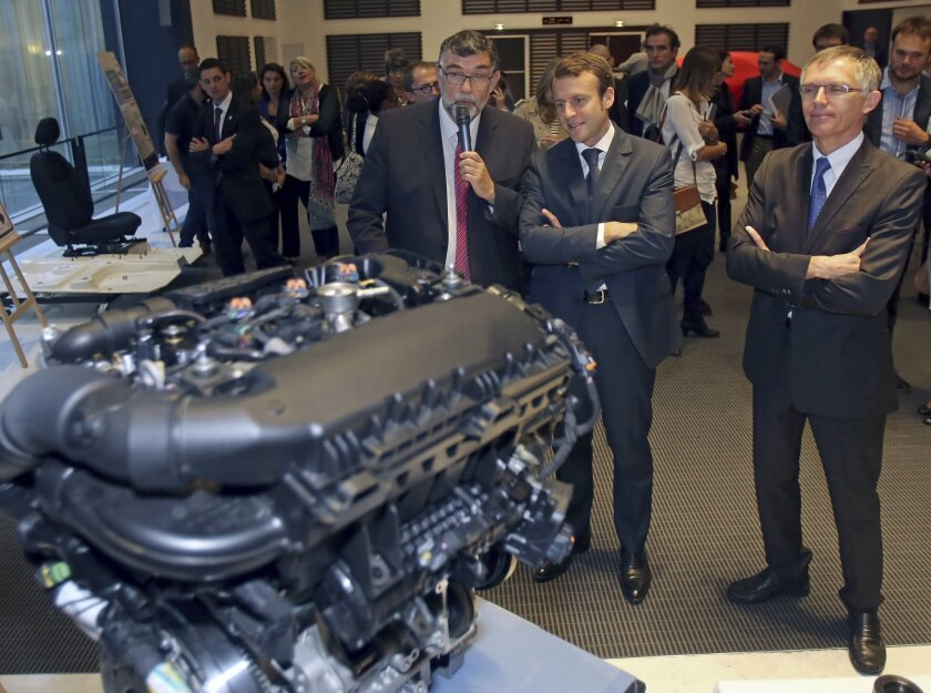 French Economy and Industry Minister Emmanuel Macron, center, listens to the explanations of PSA Peugeot research director Gilles Le Borgne, left, as they watch the EB turbo pure tech engine during his visit to the PSA Peugeot Citroen headquarters in Paris, Tuesday Sept. 30, 2014. Watching at right is PSA Peugeot Citroen chairman Carlos Tavares. (AP Photo/Remy de la Mauviniere)