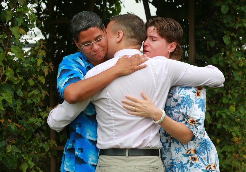 Stephanie Torres, left, and Susan Hartman hug Fernando Lopez after he performed the ceremony to marry them on the lawn of the County Administration Building Monday morning.  Numerous same-sex couples arrived to get their marriage licenses and some actually were married  as well on Monday morning at