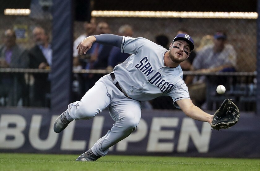 FILE - In this Sept. 19, 2019, file photo, San Diego Padres' Hunter Renfroe makes a diving catch on a ball hit by Milwaukee Brewers' Lorenzo Cain during the first inning of a baseball game in Milwaukee. The Padres have acquired outfielder Tommy Pham and infielder-pitcher Jake Cronenworth from the Tampa Bay Rays for Renfroe, minor league infielder Xavier Edwards and a player to be named. (AP Photo/Morry Gash, File)