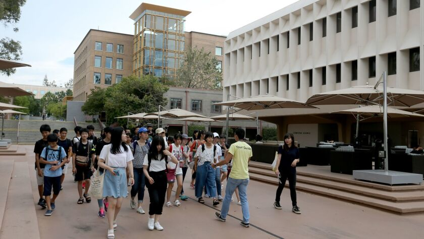 A tour guide leads a group of students past the Computer Science building and Engineering Tower at the University of California-Irvine in Irvine, Calif. on Aug. 2, 2017.