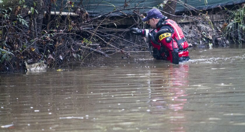 Carl Hall of Horry County Fire and Rescue searches a creek for a 5-month-old girl believed to be lost in Socastee Swamp waters Wednesday, Nov. 4, 2015, after the mother said Tuesday she'd put the baby in brown, swirling waters. The mother, Sarah Lane Toney, was charged with unlawful conduct toward