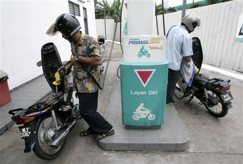 Motorcyclists fill up with gas at a gas station in Kuala Lumpur, Malaysia, Thursday, Oct. 8, 2009, a day after oil prices edged up. (AP Photo/Lai Seng Sin)