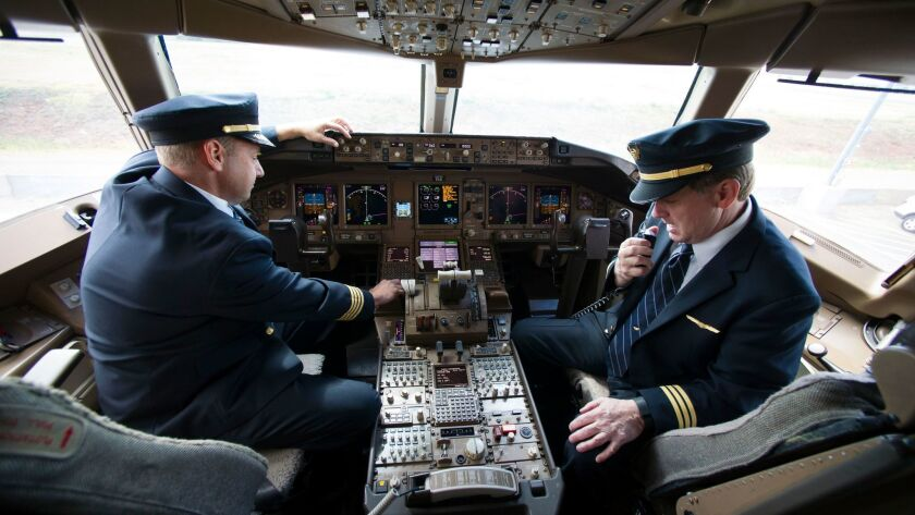 United Airlines Capt. Tommy Holloman, left, and Capt. Chuck Stewart demonstrate radio communications