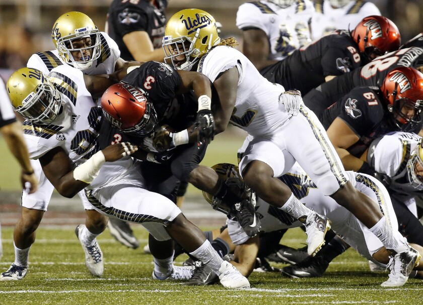 UNLV running back Lexington Thomas drives into the UCLA defense during the first half on Saturday.