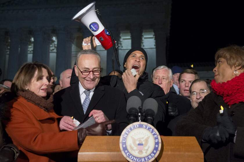 From left, House Minority Leader Nancy Pelosi, Senate Minority Leader Charles E. Schumer, Sen. Cory Booker and other Democratic lawmakers join protesters in Washington on Monday night.