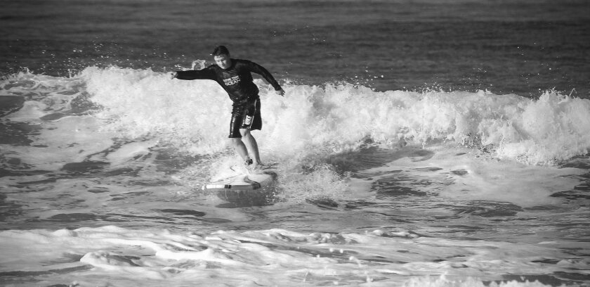 Sam rides a wave during a surfing lesson one Sunday morning near the Oceanside Harbor, in September, nearly two months after he had top surgery to remove his   breast tissue.