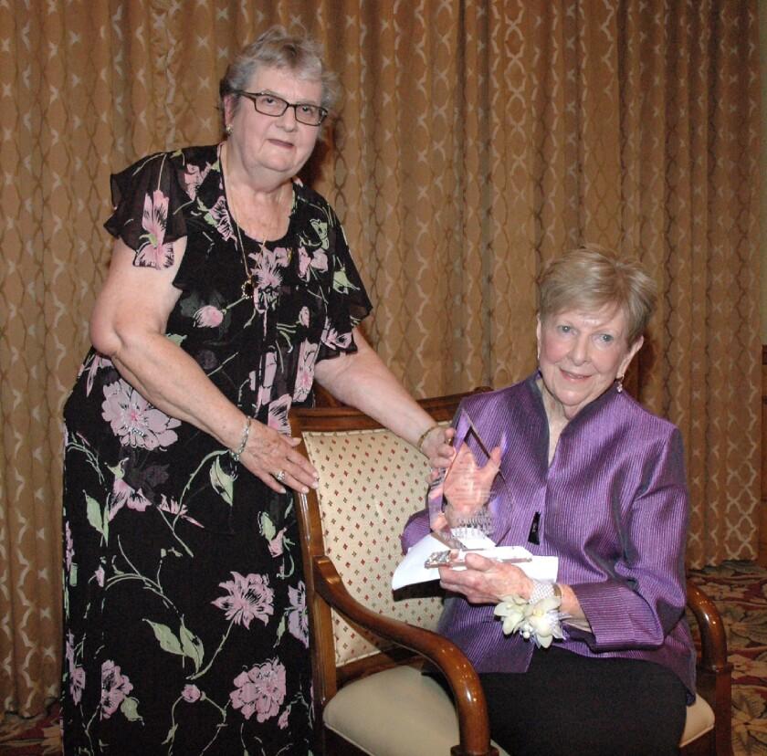 Patrons Club President Karen Wharton, left, presents Gael Davitt with the Woman of Distinction award