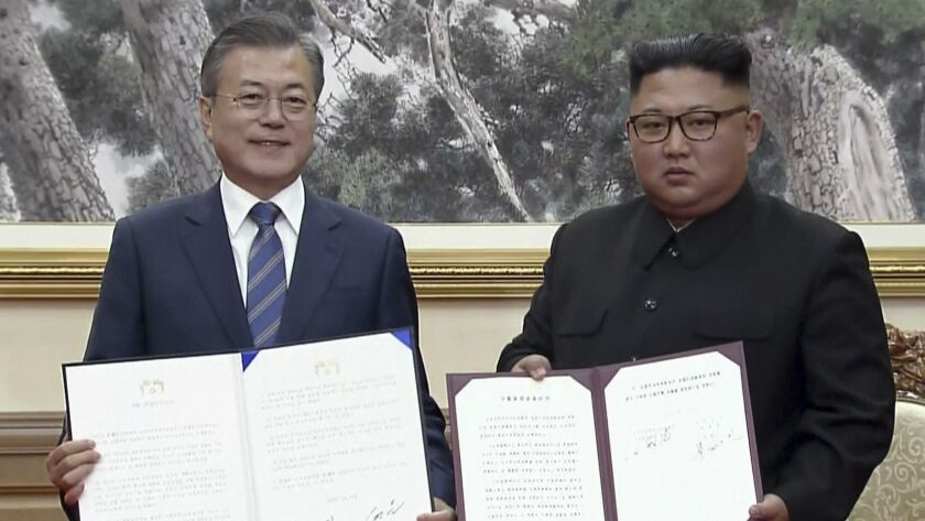 In this image made from video provided by Korea Broadcasting System, South Korean President Moon Jae-in, left, and North Korean leader Kim Jong Un pose after signing documents in Pyongyang.