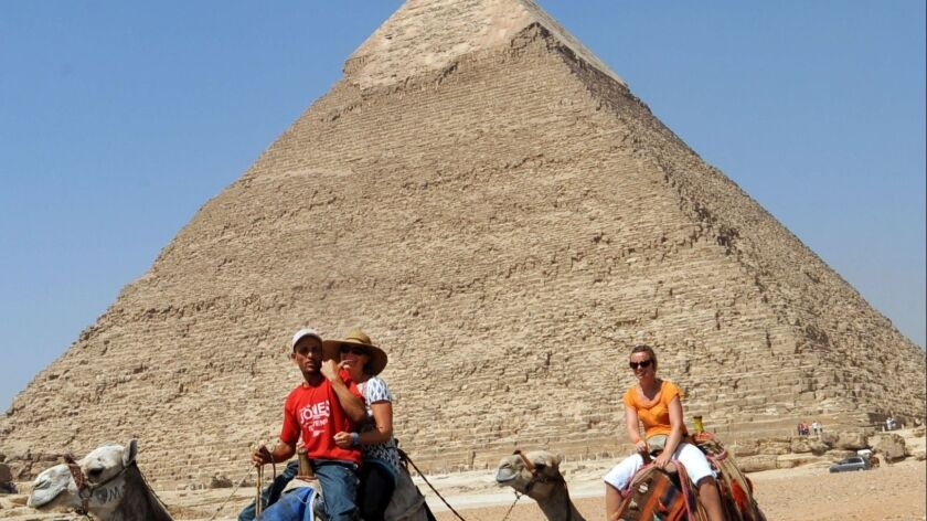 Tourists and their guide ride camels past a pyramid in Giza, Egypt.