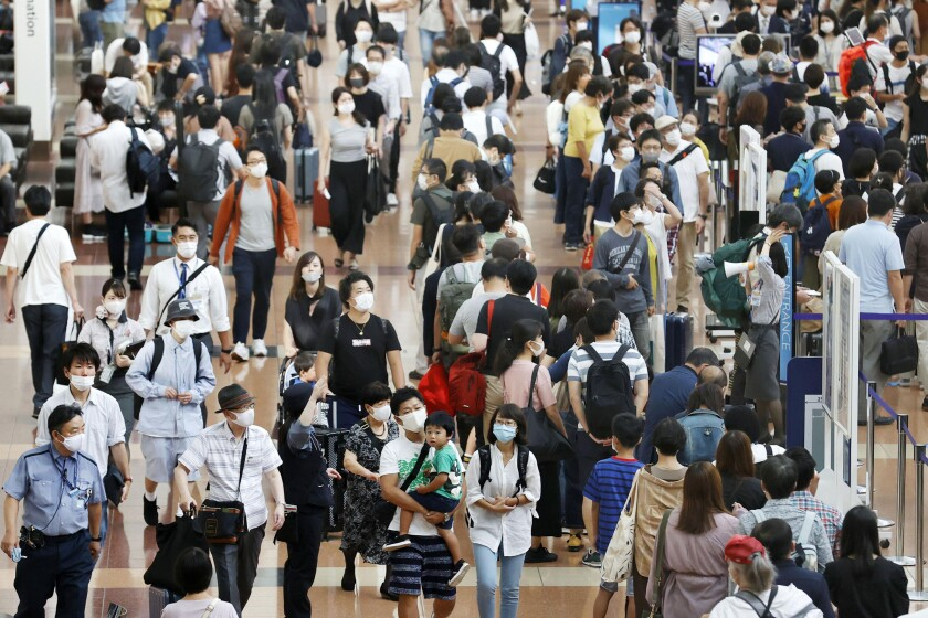 Travelers wearing face masks crowd at Haneda airport in Tokyo Saturday, Sept. 19, 2020, on the first day of the 4-day holiday. (Kyodo News via AP)