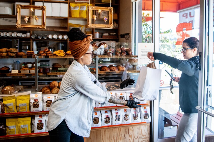 Nicole Medina brings a customer her order at Rõckenwagner Bakery & Cafe on Friday, March 27, 2020.