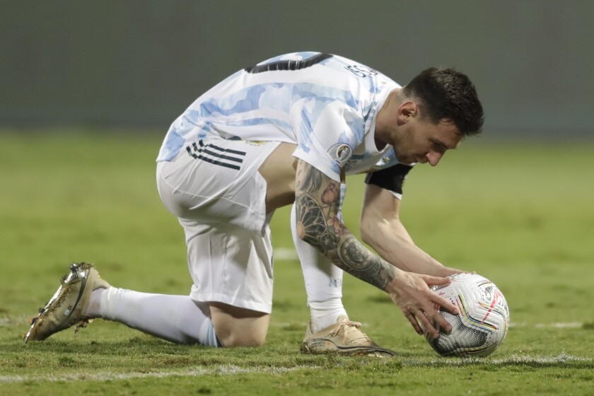 Argentina's Lionel Messi places the ball for a free kick to score his side's third goal against Ecuador during a Copa America quarterfinal soccer match at the Olimpico stadium in Goiania, Brazil, Saturday, July 3, 2021. (AP Photo/Andre Penner)