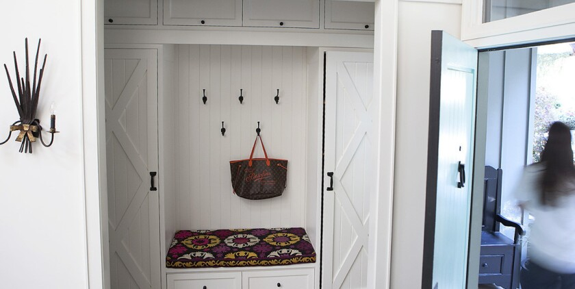 A mudroom off the entryway has cushioned seating, twin wardrobes for coats and wall hooks to hang hats and purses.