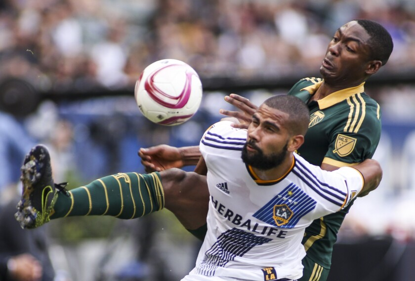 Galaxy defender Leonardo and Portland Timbers forward Fanendo Adi (9) in action during an MLS match on Oct. 18.