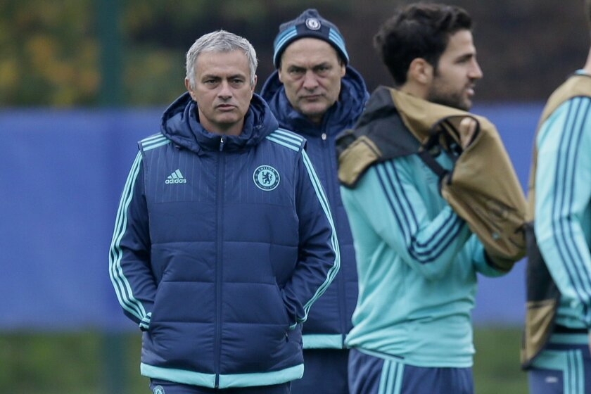 Chelsea Manager Jose Mourinho, left, stands with assistant first team coach Silvino Louro, centre, and Cesc Fabregas during a training session at their training ground in Cobham, England, Tuesday Nov. 3 2015. Chelsea will play Dynamo Kyiv in a Group G match on Wednesday. (AP Photo/Tim Ireland)