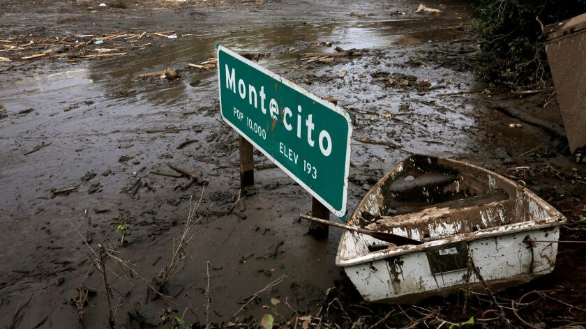A sign on the 101 Freeway in Montecito is nearly submerged by mud and debris on Jan. 15.