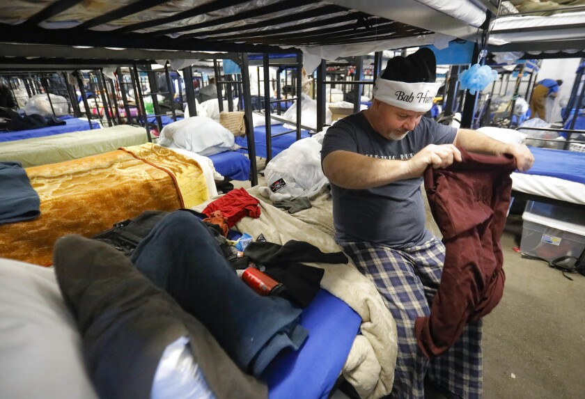 In this photo from December 2018, David Hudson is seen preparing his bunk at the Alpha Project bridge shelter on Newton Avenue and 16th Street in San Diego. The city is moving women out of the shelter to create more space between bunks as a precaution during the coronavirus outbreak.