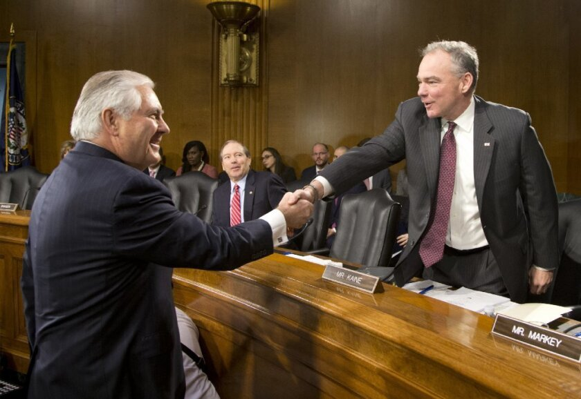 Senate Foreign Relations Committee member Sen. Tim Kaine (D-Va.), right, greets Secretary of State-designate Rex Tillerson on Capitol Hill at the start of his confirmation hearing on Jan. 11.