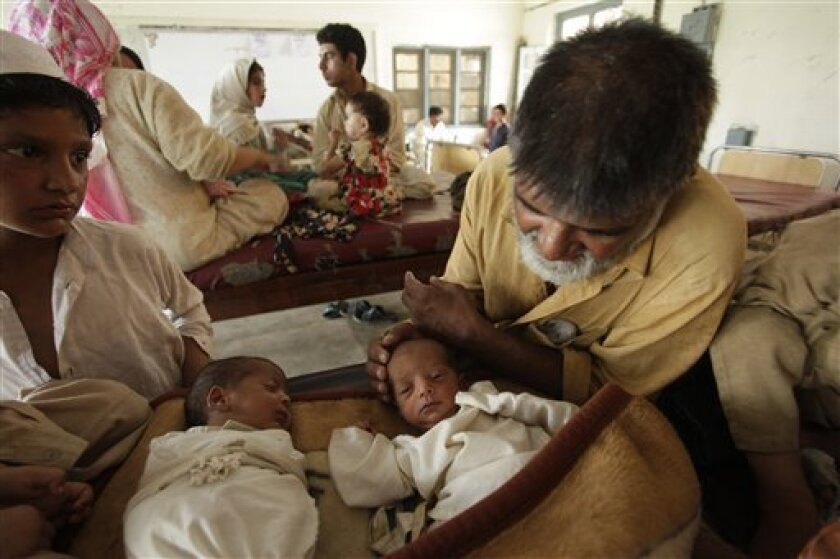 A Pakistani father, right, who is displaced by heavy floods, looks at his twins born in a camp set up in Nowshera in northwest Pakistan on Monday, Aug.9, 2010. Pakistan will need billions of dollars to recover from its worst floods in history, further straining a country already dependent on foreig