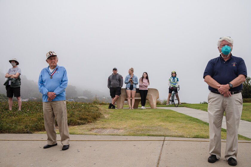 A few spectators watch at a distance during a Memorial Day service May 25 at Mount Soledad National Veterans Memorial in La Jolla. Due to restrictions caused by the coronavirus pandemic, the remembrance was shown online and not open to the public.