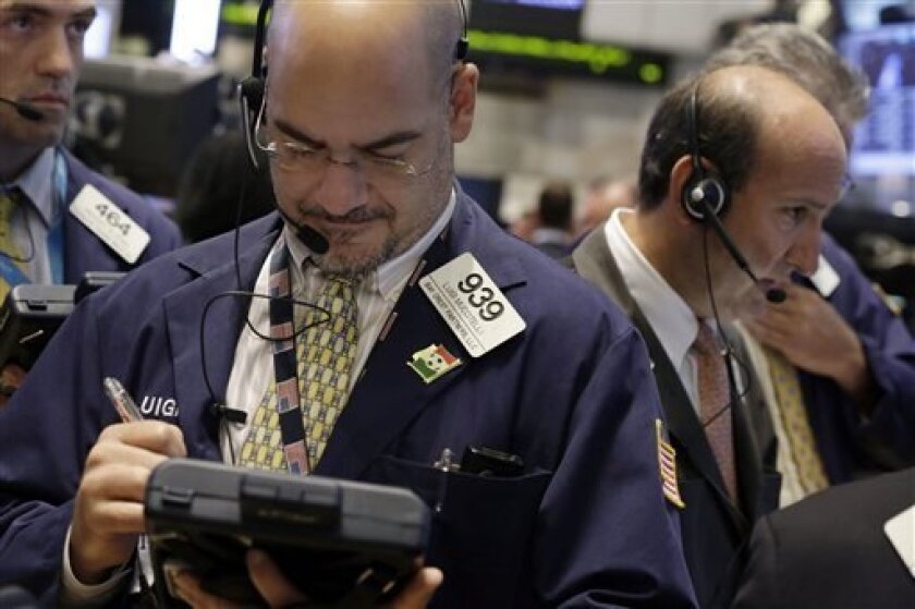 In this Tuesday, Aug. 27, 2013 photo, Luigi Muccitelli, center, works with fellow traders on the floor of the New York Stock Exchange. Asian markets were little changed in trading Friday Sept. 13, 2013 as investors awaited a decision from the U.S. on a possible attack on Syria as well as on stimulus measures. (AP Photo/Richard Drew)